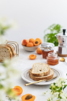 Splendidamente servita colazione estiva con pane tostato e marmellata di albicocche fatta in casa