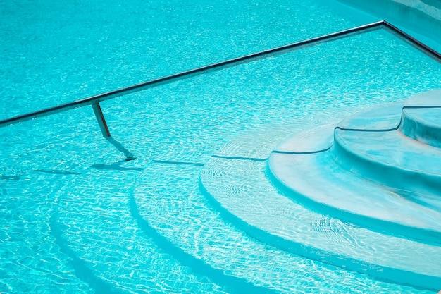 Gradini meravigliosamente eleganti della scala in una piscina sullo sfondo del mare della natura