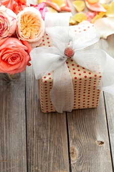 Scatola regalo splendidamente incartata e rose fresche