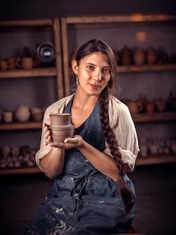 Beautifulpottery girl crea una nuova ceramica dall'argilla su un tornio da vasaio