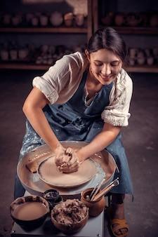 Beautifulpottery donna sta lavorando al tornio. produzione artigianale.