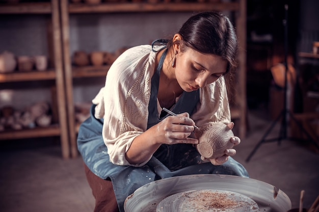 Beautifulyoung woman master dimostra il processo di realizzazione di piatti in ceramica utilizzando la vecchia tecnologia. artigianato popolare.