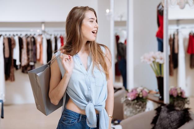 Beautiul ha sorpreso la giovane donna con la borsa della spesa e in piedi nel negozio di abbigliamento