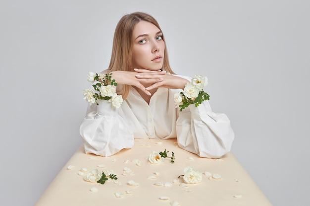 Ritratto di arte di bellezza di una donna con fiori di rosa nelle sue mani. cosmetici naturali per mani e viso