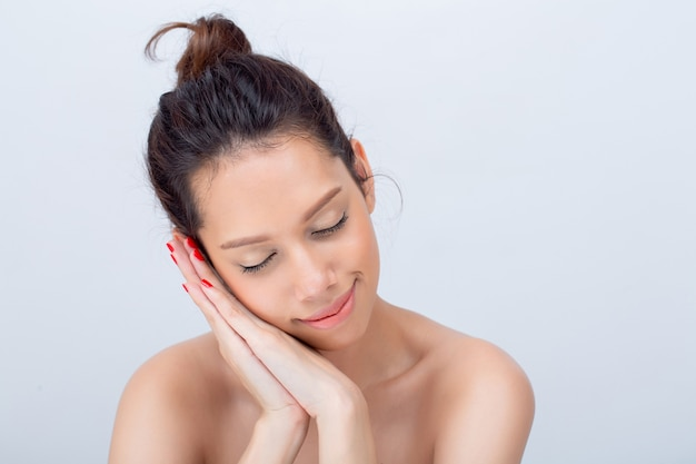 Modello di moda asiatico della giovane donna di bellezza con trucco naturale del fronte a forma di v su bianco