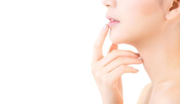 La giovane donna asiatica di bellezza con la pelle pulita fresca tocca le labbra