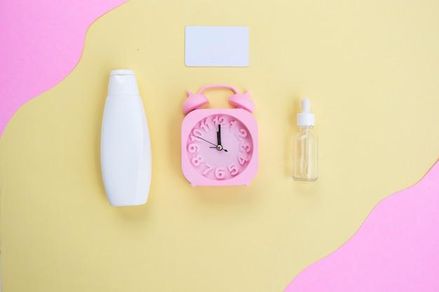 Sfondo di bellezza di flaconi cosmetici e sveglia su sfondo di carta gialla e rosa. concetto di cura della pelle estiva