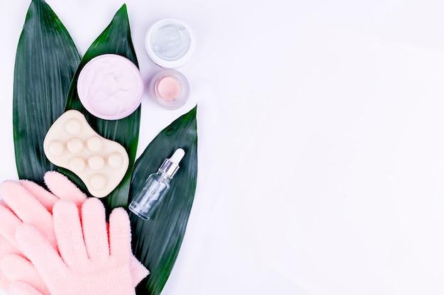 Sfondo di bellezza con prodotti cosmetici per il viso, grandi foglie verdi sullo sfondo. layout moderno per la cura della pelle primaverile, vista dall'alto, piatto