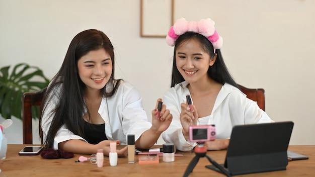 Concetto di blogger di bellezza, video di registrazione del prodotto regalo di revisione della donna compongono il cosmetico del rossetto a casa.