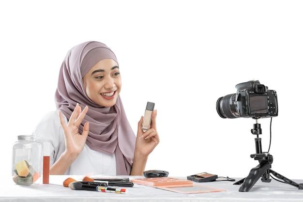 Beauty blogger in hijab con in mano una bottiglia di rossetto che registra video con la fotocamera