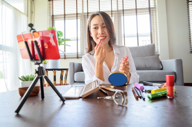 Beauty blogger influencer donna asiatica che utilizza lo smartphone in live streaming recensisce i prodotti cosmetici nel soggiorno di casa