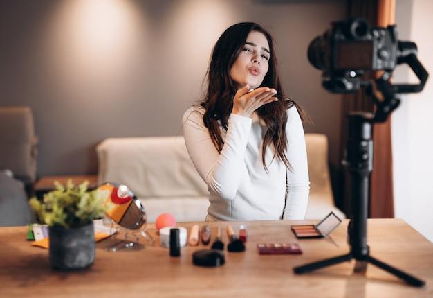 Blogger di bellezza bella femmina che filma tutorial di routine di trucco quotidiano sulla macchina fotografica. influencer giovane donna live streaming recensione di prodotti cosmetici in home studio. lavoro da vlogger. fai da te mettendo il trucco.