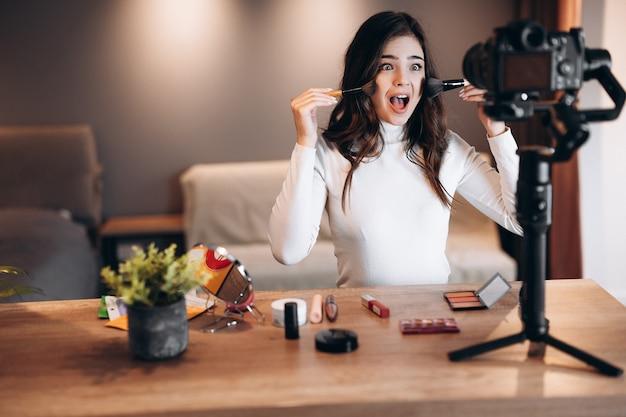 Blogger di bellezza bella femmina che filma tutorial di routine di trucco quotidiano e si diverte con la fotocamera influencer giovane donna live streaming recensione di prodotti cosmetici in home studio lavoro vlogger fai da te mettendo makeu