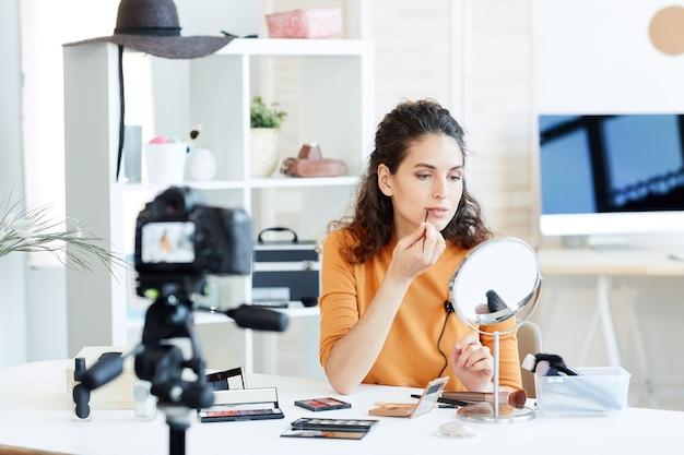 Blogger di bellezza che si siede al tavolo davanti allo specchio che applica matita per labbra sulla macchina fotografica, colpo orizzontale