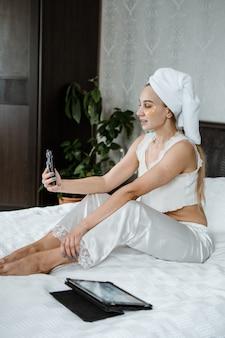 Beauty blogger, vlogger, influencer. giovane donna in pigiama, asciugamano sulla testa e con cerotti cosmetici al collagene sotto gli occhi che registrano video clip su tablet. spa, cura della pelle e benessere.