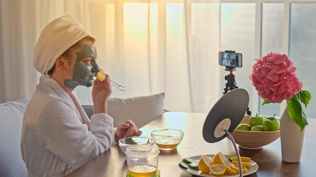 Un blogger di bellezza in una veste bianca con un asciugamano bianco sulla testa si applica una maschera idratante verde sul viso e blog sulla cura della pelle e sui cosmetici. la prossima generazione di influencer di bellezza