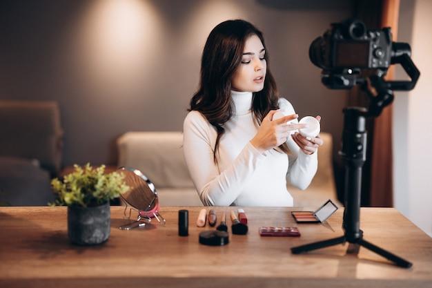 Donna di blogger di bellezza che filma tutorial di routine di trucco quotidiano sulla fotocamera. influencer giovane donna live streaming recensione di prodotti cosmetici in home studio. lavoro da vlogger. fai da te.