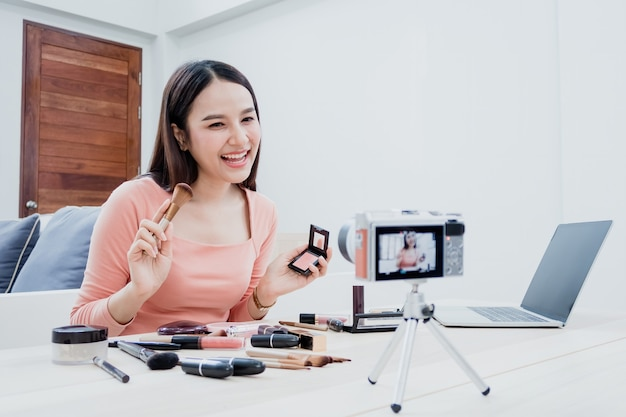 Blogger di bellezza, belle donne asiatiche stanno cercando di capire e vendere cosmetici. tramite streaming online utilizzando una fotocamera e un laptop con una faccia sorridente felice, una nuova attività normale