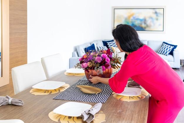 La bellezza della donna bruna con i capelli lunghi e il vestito rosso sta decorando la tavola con una composizione floreale all'interno di una zucca dipinta colorata per celebrare un halloween diverso different