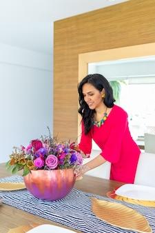 La bellezza della donna bruna con i capelli lunghi e il vestito rosso sta decorando la tavola con una composizione floreale all'interno di una zucca dipinta colorata per celebrare un halloween diverso