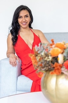 Bellezza donna bruna con capelli lunghi e vestito rosso seduti insieme a una composizione floreale all'interno di una zucca dipinta colorata per celebrare un diverso halloween to
