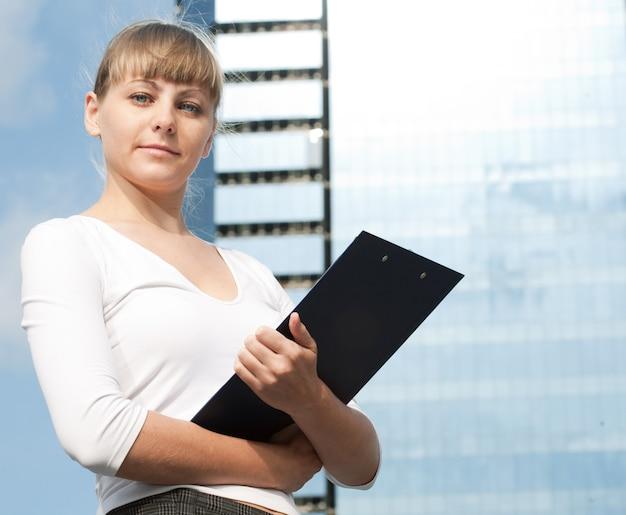 Donna d'affari di bellezza su un moderno edificio in vetro con documento