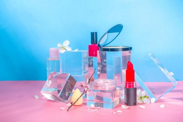 Cura della bellezza, cosmetici per il trucco su podi con piedistalli in vetro trasparente, mock up su uno sfondo blu rosa brillante con fiori di ciliegio primaverile