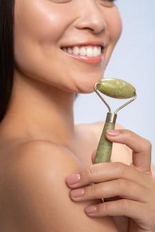 Cure di bellezza. felice giovane donna che mantiene il sorriso sul viso, facendo un massaggio facciale