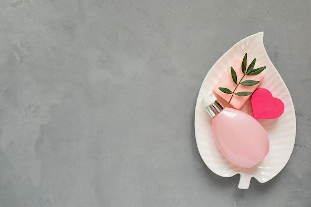 Prodotti per la cura della bellezza, crema o siero nella bottiglia rosa, sapone e spugna a forma di cuore sul piatto a forma di foglia