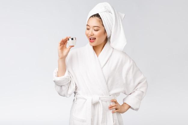 Concetto di bellezza donna graziosa asiatica con pelle perfetta che tiene bottiglia cosmetica