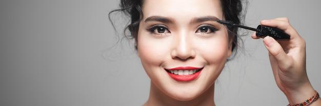 Concetto di bellezza, donna asiatica con gli occhi chiusi che tiene mascara vicino agli occhi