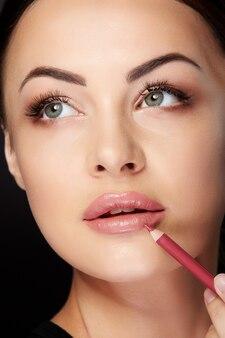 Concetto di bellezza, ritratto del primo piano della donna che mette il trucco, dipingendo le labbra con il rossetto rosso. ritratto di donna che tocca le labbra con la matita e alzando lo sguardo, studio, sfondo nero