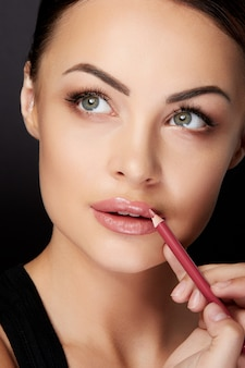 Concetto di bellezza, testa e spalle della donna che disegna il contorno sulle labbra con il rossetto rosso. ritratto di modello toccando le labbra con la matita e alzando lo sguardo, studio, sfondo nero
