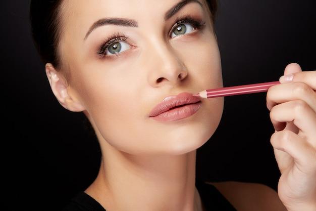 Concetto di bellezza, testa e spalle della donna che disegna il contorno sulle labbra con il rossetto rosso. ritratto di donna che tocca le labbra con la matita e alzando lo sguardo, studio, sfondo nero