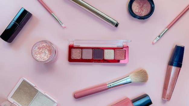 Concetto di bellezza. prodotti per il trucco ombre, evidenziatore, fard, pennelli, cipria, glitter, mascara, gloss, rossetto, matita su sfondo rosa. tema delle vendite, venerdì nero, shopping di cosmetici.