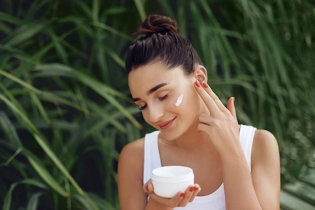 Concetto di bellezza. ritratto di bella donna che applica crema cosmetica sul viso e sorridente. cura del corpo e della pelle