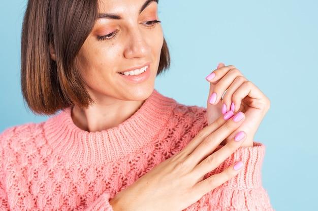 Concetto di bellezza, bella donna con unghie color rosa brillante manicure sulla parete