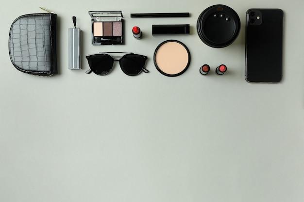 Concetto di bellezza con cosmetici per il trucco su grigio
