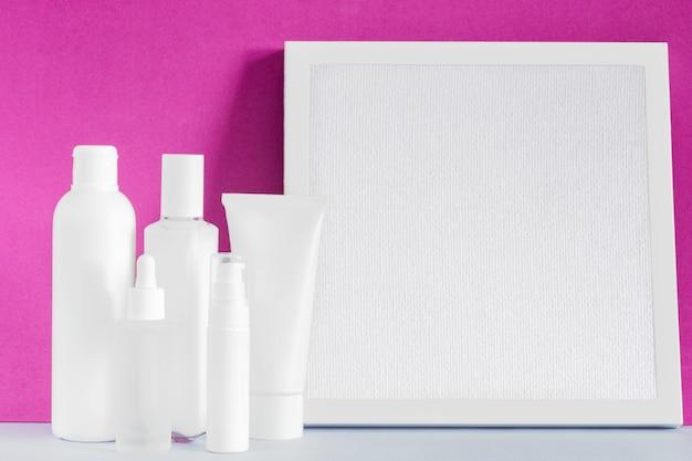 Mockup di prodotti cosmetici di bellezza. mock up prodotto per la cura della pelle. bordo del telaio della tela. flaconi di olio di siero spray per lozione crema. concetto di cura della pelle