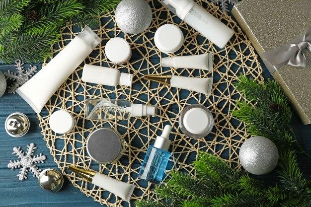 Prodotti cosmetici di bellezza con decorazioni natalizie su stuoia di vimini