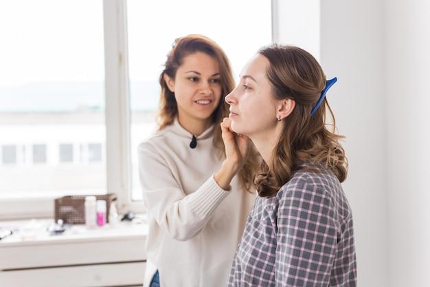Concetto di bellezza e cosmetici - make-up artist che fa trucco professionale di giovane donna