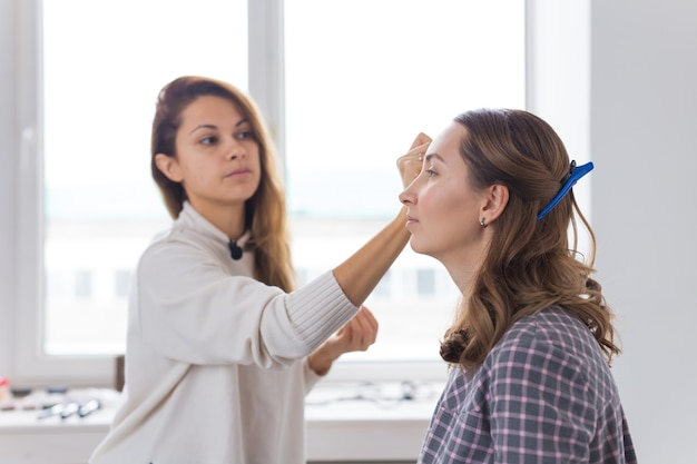 Concetto di bellezza e cosmetici - artista di trucco che fa trucco professionale di giovane donna