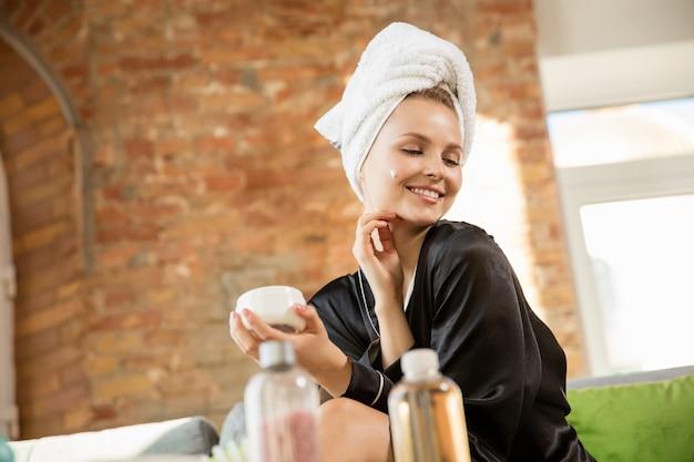 Giornata della bellezza. donna che indossa abito di seta facendo la sua routine quotidiana di cura della pelle a casa. sembra soddisfatta, si mette la crema idratante sulla pelle del viso, sorride. concetto di bellezza, cura di sé, cosmetici, giovinezza.