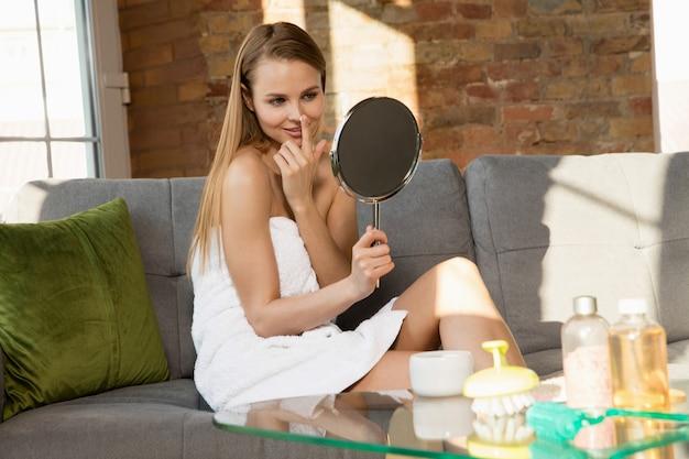 Giornata della bellezza. donna che indossa un asciugamano facendo la sua routine quotidiana di cura della pelle a casa. mettere su crema idratante e crema, guardando il suo riflesso nello specchio. concetto di bellezza, cura di sé, cosmetici, giovinezza.