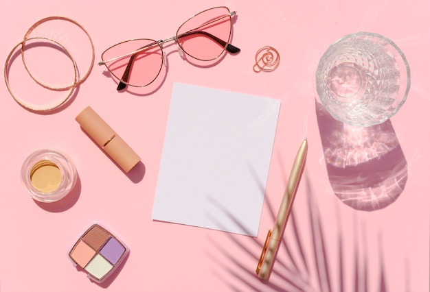 Vista dall'alto del desktop di bellezza con cosmetici, ombre di palma e foglio di carta