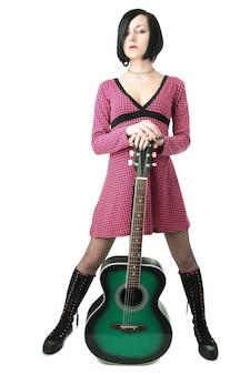 Ragazza emo di bellezza con la chitarra su sfondo nero