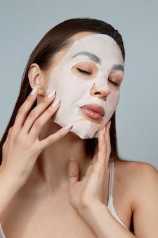 Cura della pelle del viso di bellezza. la donna applica una maschera idratante in panno sul viso. modello di ragazza con maschera cosmetica. trattamento facciale