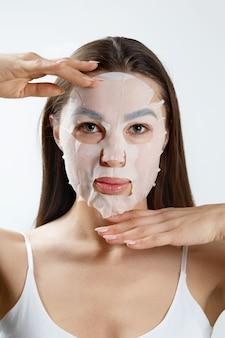 Maschera facciale di bellezza. bella giovane donna con una maschera idratante di panno sul viso. cura della pelle. maschera termale cosmetica. trattamento facciale