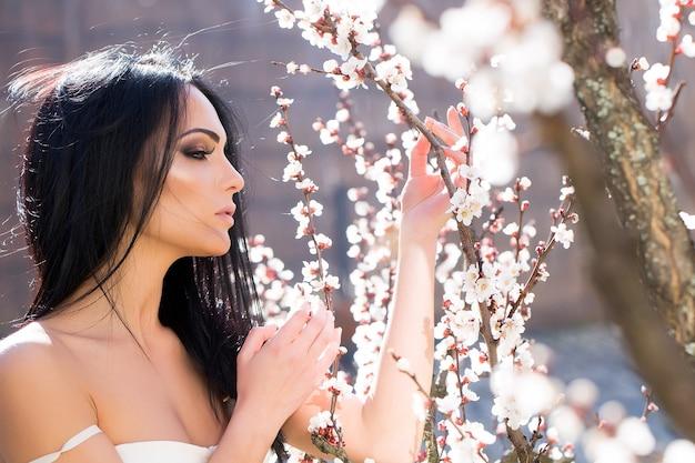 Bellezza e moda bella donna vicino al parco di fioritura primaverile