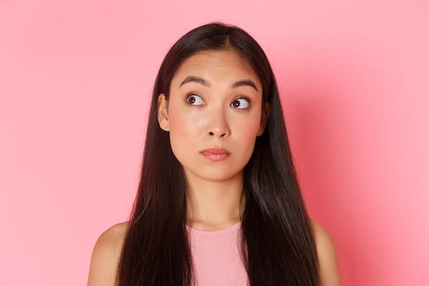 Concetto di bellezza, moda e stile di vita. close-up di indecisa, bella ragazza asiatica che sembra confusa nell'angolo in alto a sinistra, sentendosi perplessa o esitante, facendo la scelta sul muro rosa